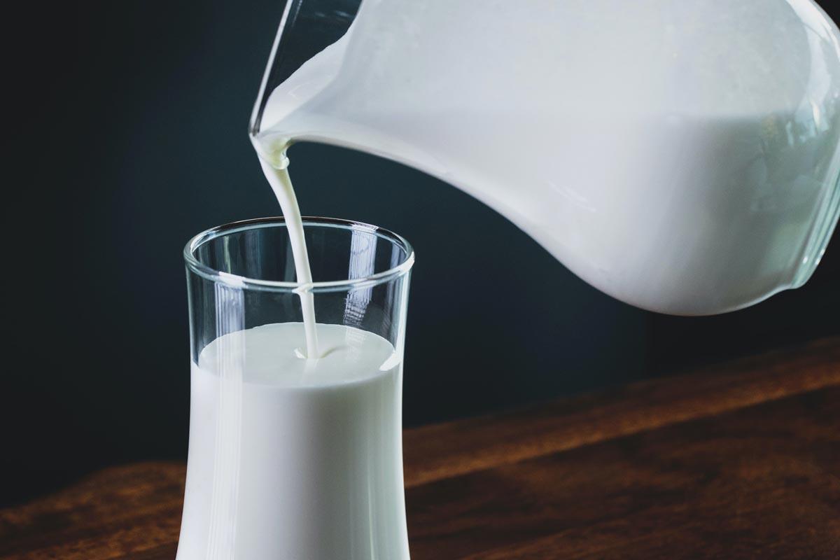 Ein Glas mit Milch wird eingeschenkt